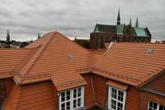 Das 2017 fertiggestellte, neu eingedeckte Dach des Haupthauses mit der Katherienkirche im Zentrum und der Ägidienkirche und den zwei Türmen des Doms im Hintergrund.